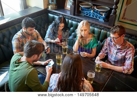 people, leisure, friendship and communication concept - friends with smartphones drinking beer and texting at bar or pub