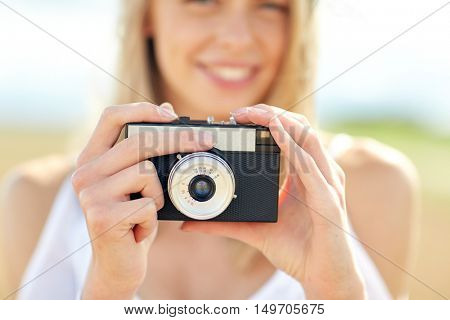 photography, summer holidays, vacation and people concept - close up of young woman taking picture with film camera outdoors