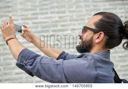 leisure, technology and people concept - hipster man taking picture or video by smartphone on street
