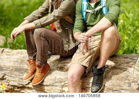 travel, hiking, backpacking, tourism and people concept - close up of couple resting on tree trunk outdoors