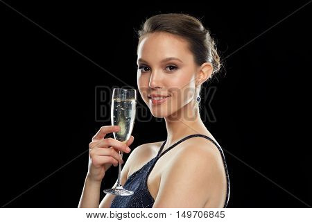 holidays, nightlife, drinks, people and luxury concept - smiling beautiful young asian woman drinking champagne at party over black background and spotlights