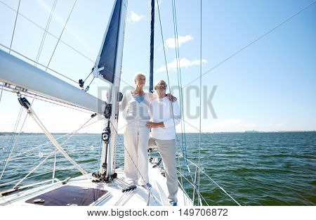 sailing, age, tourism, travel and people concept - happy senior couple hugging on sail boat or yacht deck floating in sea