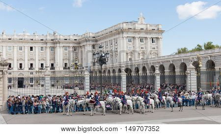 Madrid - 7 October 2015: Tourists gathered around Madrid's Royal Palace and a ceremony is held - changing of the guard guardsmen and white horses October 7 2016 Madrid Spain