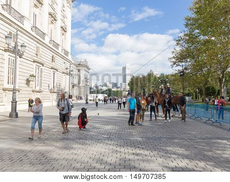 Madrid - 7 October 2015: Tourists walk around and take pictures of the Royal Palace of Madrid and the police on horses follow the order of 7 October 2016 Madrid Spain