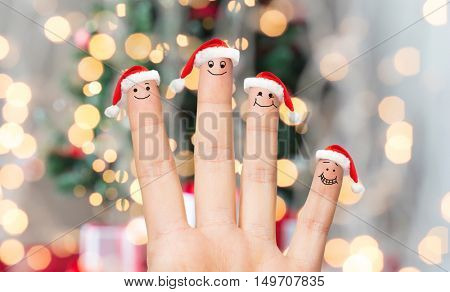 family, holidays, christmas and body parts concept - close up of hand with four fingers in santa hats with smiley faces over lights background