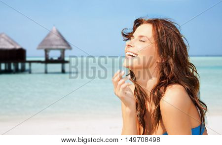 travel, tourism, summer vacation and people concept - happy beautiful woman over tropical beach with bungalow background