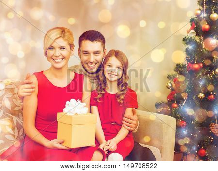 family, christmas, x-mas, winter, happiness and people concept - smiling family at home with gift box