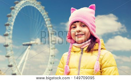 childhood, tourism, travel, vacation and people concept - happy beautiful little girl over london ferry wheel background
