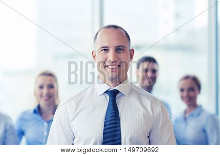 business, people and teamwork concept - smiling businessman with group of businesspeople in office