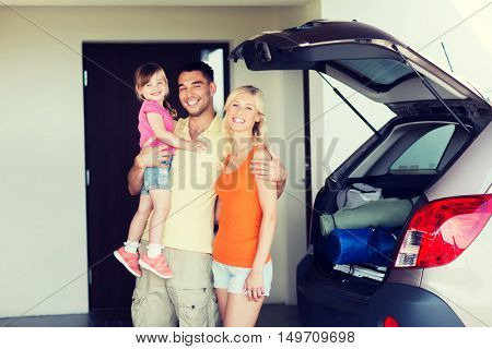 transport, leisure, road trip, travel and people concept - happy family with little girl packing things hatchback car at home parking space
