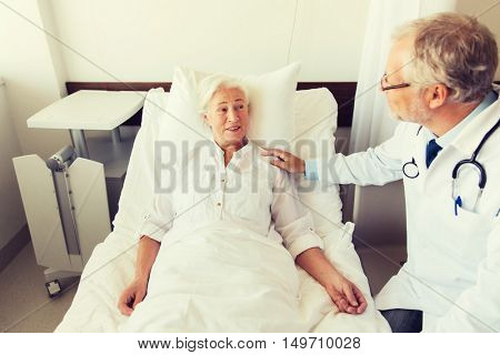 medicine, age, support, health care and people concept - doctor visiting and cheering senior woman lying in bed at hospital ward