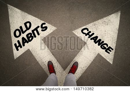 OLD HABITS versus CHANGE written on the white arrows dilemmas concept.