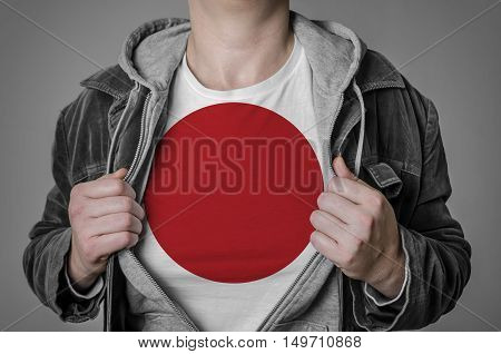 Man showing Japan flag on t-shirt. Concept for patriotism freedom and national pride.
