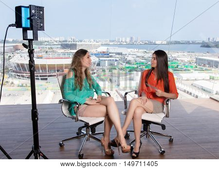 Beautiful female presenter interviewing a famous woman