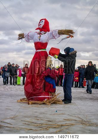 Saint-Petersburg Russia - February 22 2015: Feast Maslenitsa on Vasilyevsky Island. Burning doll - a doll ready organizers Doll pour flammable liquid.