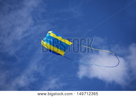 kite yellow and blue in the wind against the sky with clouds kite festival in Luebeck Travemuende the famous seaside resort on the Baltic Sea generous copy space