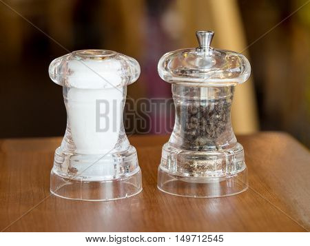 Pepper and salt in glass bottle on wood table. Ingredient for food meal.
