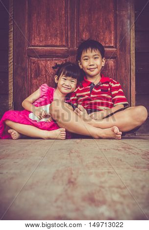 Asian kindly brother with his sister sitting and smiling happy together. Concept about loving and bonding of sibling. Happy family spending time together. Vintage tone effect.