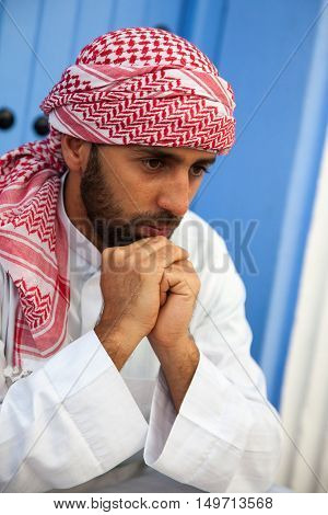 Portrait of young handsome arabic man wearing traditional clothes