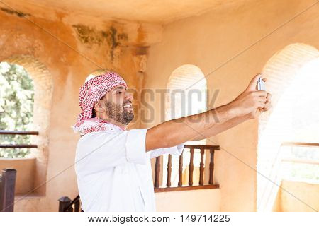 Young smiling handsome arabic man in traditional clothes takes selfie smartphone