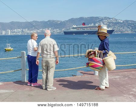 ACAPULCO MEXICO - MARCH 11 2006 : A Mexican selling hats to tourists with Queen Mary 2 cruise ship in the background in Acapulco Mexico.