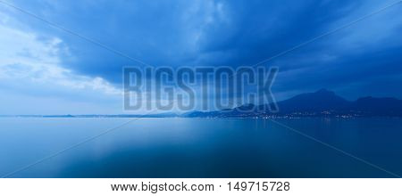 Lago di Garda in the evening (Garda Lake) the largest Italian lake of glacial origin with the lights of the coast of Lombardy Italy