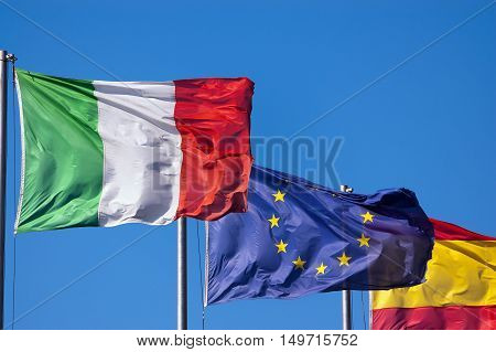 Italian European and Spanish flags hanging from a pole flowing in the wind on a clear blue sky