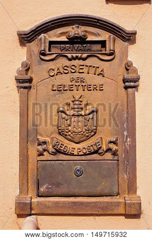 Detail of an Italian old and rusty metal mailbox embedded in a wall with text Private deposit box for letters royal mail. Italy