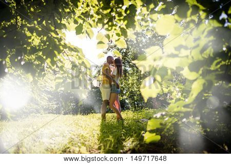 Young man carrying her girlfriend on hands - outdoor in nature