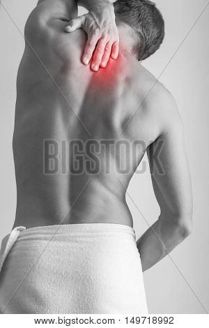 Young adult Caucasian man with backache. Black and white stylized photo with red local pain spot over back