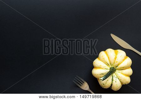 Decorative Pumpkin And Cutlery On The Black Table
