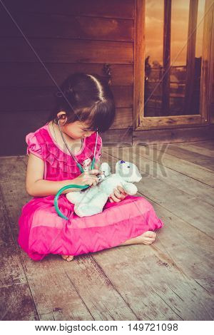 Adorable Asian Girl Playing Doctor Or Nurse With Plush Toy Bear At Home. Vintage Tone Effect.