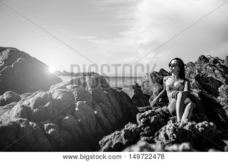 Young Brunette Girl Relaxing On The Stones