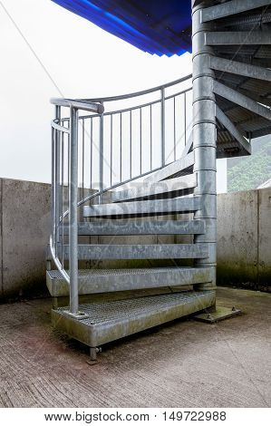 a metal spiral staircase that leads to a higher platform