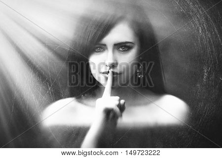 Young Woman With Dark Long Hair Saying Shh With Forefinger On Lips. Silence Gesture