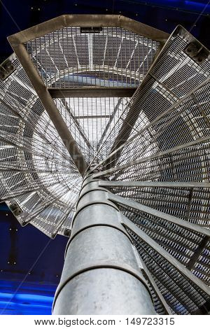 an metal spiral staircase that leads to a higher platform