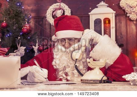 Portrait Of Santa Claus On The Phone At His Home Compiles The Wishlist For Christmas