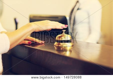 Picture of guest using bell at reception desk in hotel