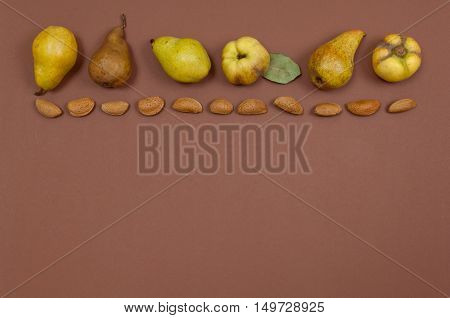Pears and quince in shell almonds in row on yellow background with copy space
