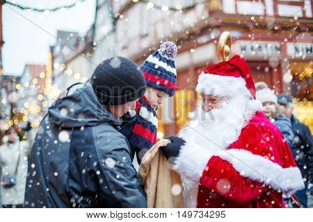 Little toddler boy with father on Christmas market. Funny happy kid taking gift from bag of Santa Claus. holidays, christmas, childhood and people concept