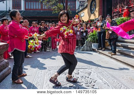 Shanghai China - October 26 2013: Chinese woman dancing with flowers near the Jade Buddha Temple in Shanghai China. Buddhism is enjoying a revival in modern liberal China.