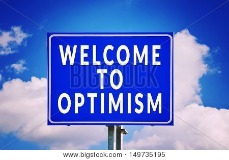 Welcome to optimism road sign with cloud background