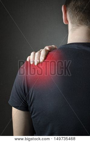 Back view of a Man with neck pain over dark background. Concept with highlighted glowing red spot.