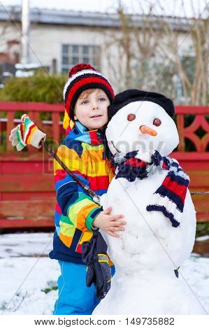 Funny kid boy in colorful clothes making a snowman, playing and having fun with snow, outdoors  on cold day. Active outoors leisure with children in winter.