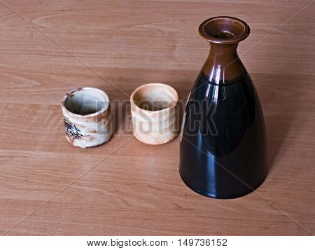 A  pitcher and two cups for the sake, standing on a wooden table