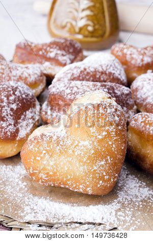 tasty heart shaped donuts with powdered sugar
