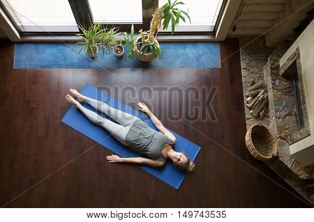 Attractive young woman working out in living room, doing yoga exercise on blue mat, lying in Shavasana Corpse, Dead Body Posture , resting after practice, meditating, breathing. Full length, top view