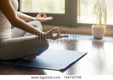 Attractive young woman working out at home, doing yoga exercise on blue mat, sitting in Easy Decent, Pleasant Posture , meditating, breathing, relaxing. Body close-up, focus on hand