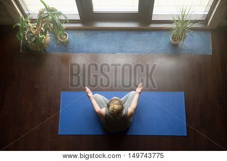 Attractive young woman working out at home, doing yoga exercise on blue mat, sitting in Easy Decent, Pleasant Posture , meditating, breathing, relaxing with closed eyes. Full length. Top view
