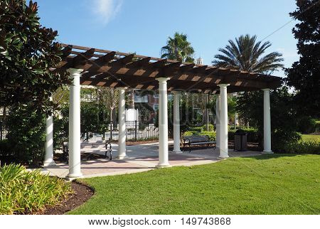 outdoor pavilion with a wood roof and columns. There are benches under the pavilion and it is surrounded by lush vegitation